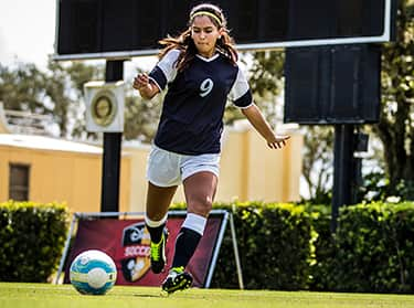 A female soccer player, with the number '9' on her jersey, prepares to kick a soccer ball
