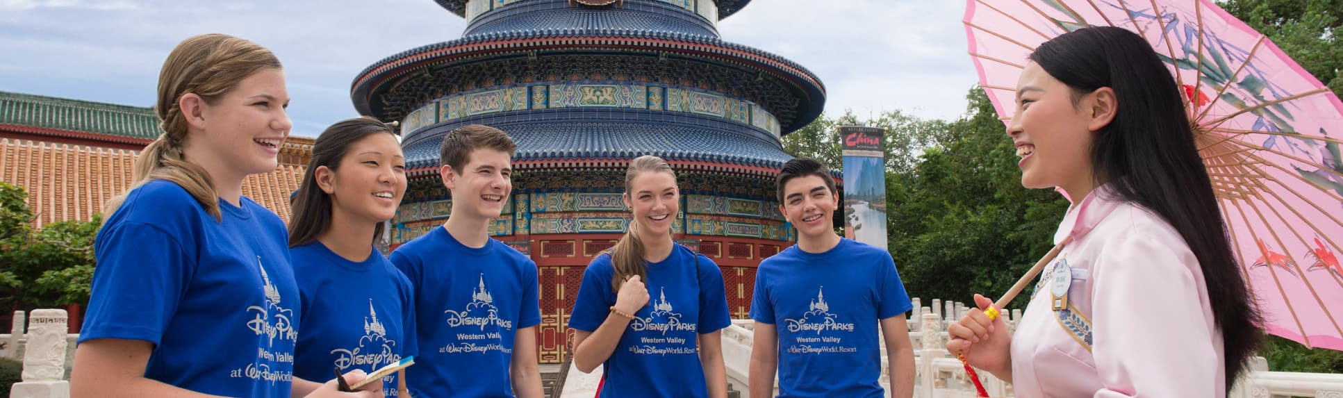 5 students with a woman dressed in traditional garb in front of the China Pavilion at Epcot
