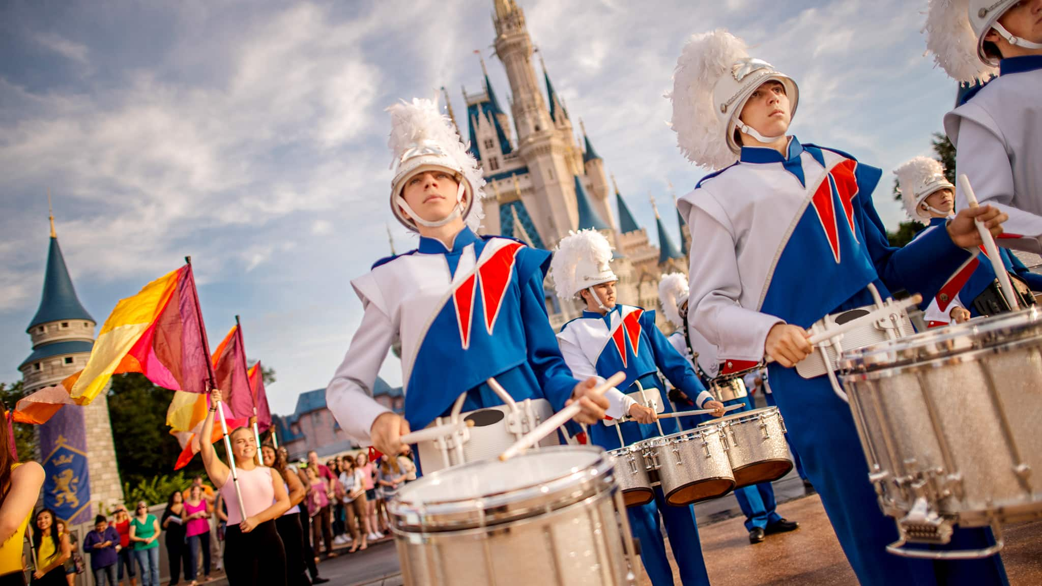 Young performers wearing uniforms playing drums and carrying flags while performing for Guests