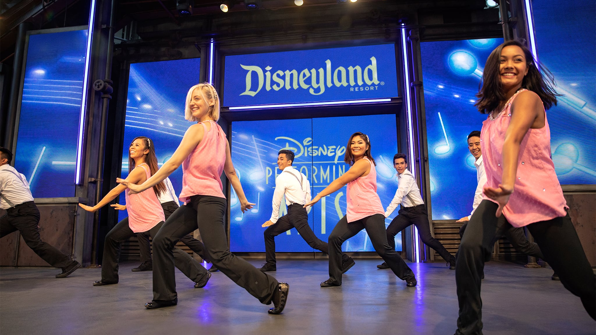 Young men and women dancing in a choreographed routine on a stage with a backdrop reading Disneyland Resort Disney Performing Arts