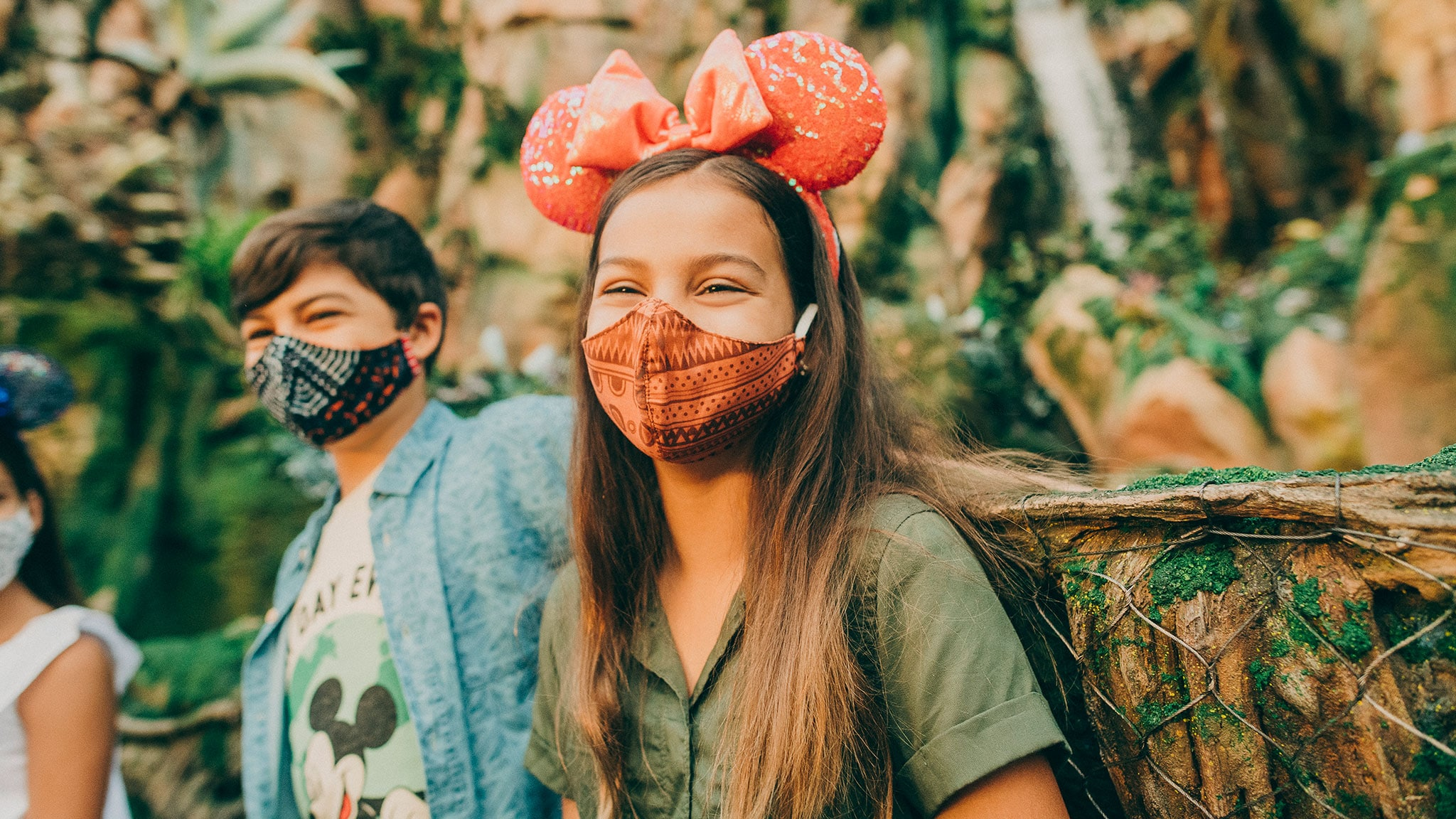 A young girl wearing a mask and Minnie Mouse sequined ear headband with a bow sits next to a young boy also wearing a mask