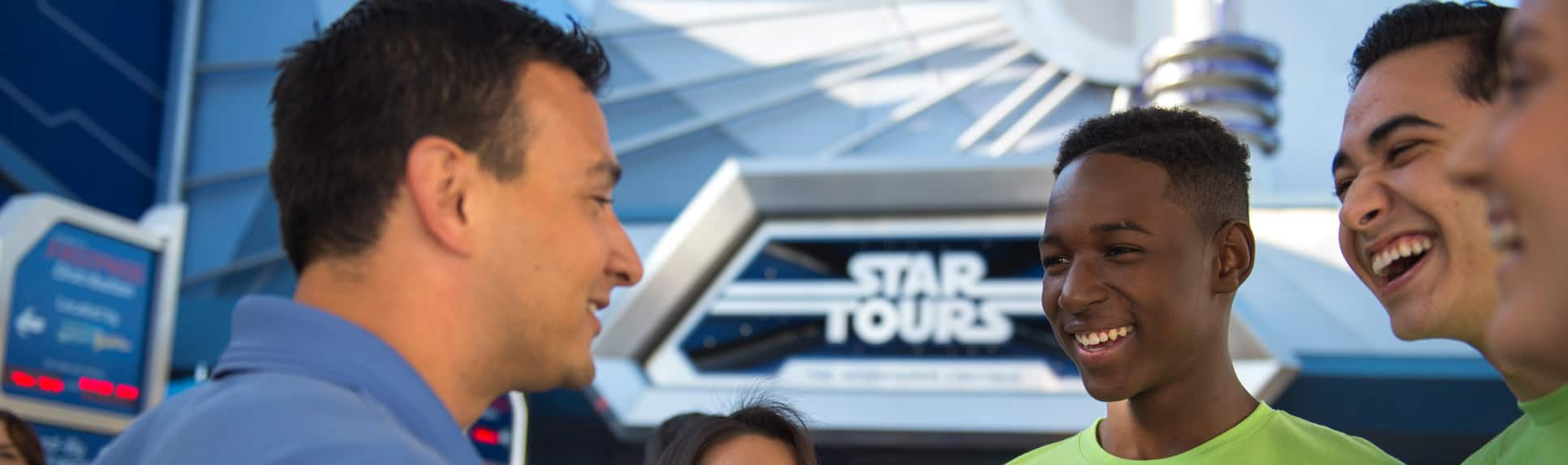 Two boys share a laugh with an adult by the Star Tours attraction