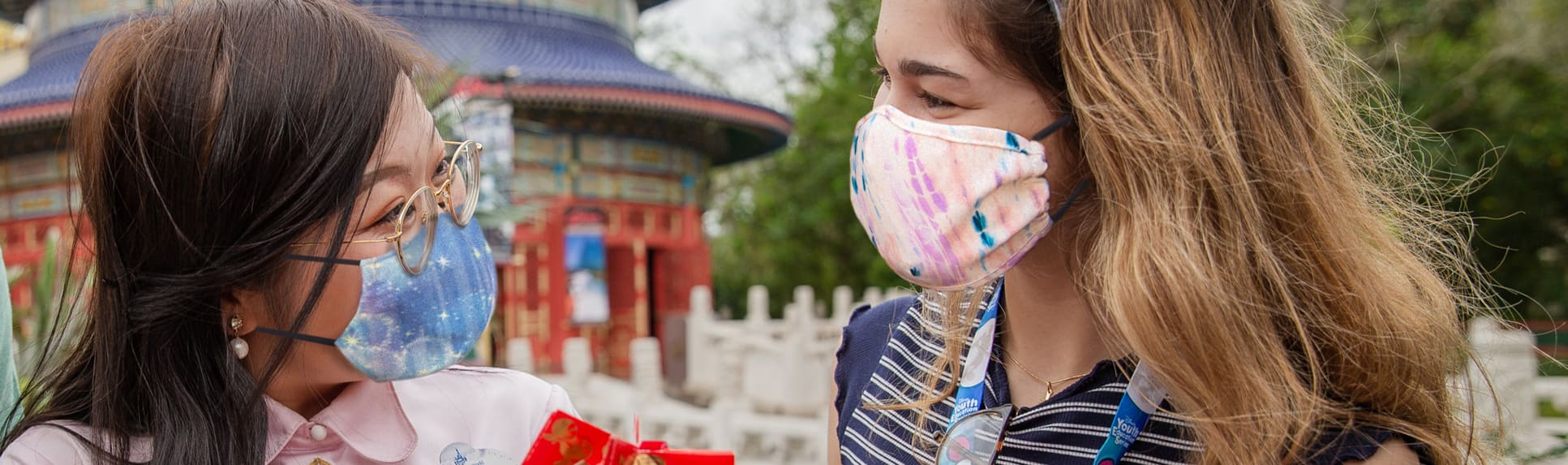 A Cast Member wearing a mask and a badge that reads 'Ningjie' shows an origami design to another woman wearing a mask in front of a building at the China Pavilion at Epcot