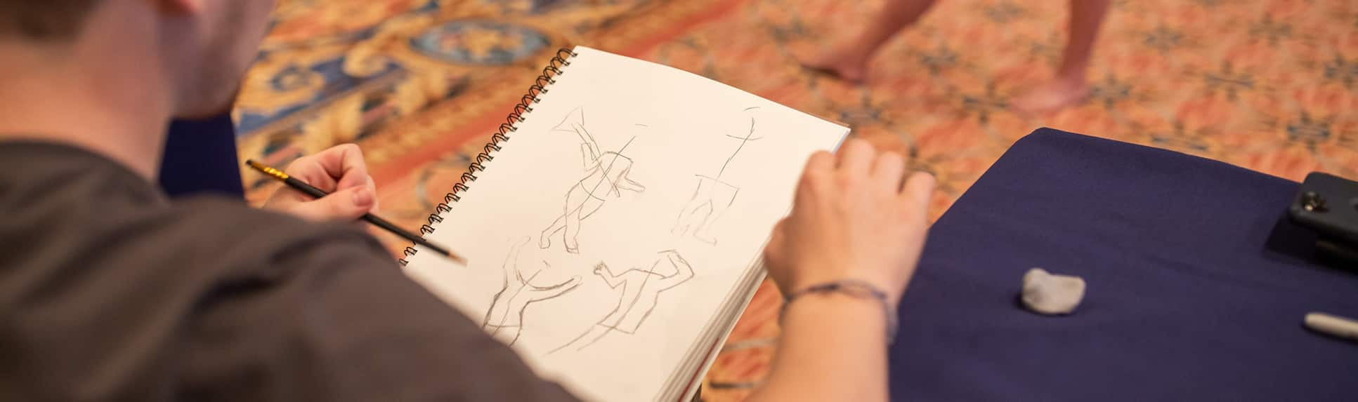 A teenage boy sketches in a pad, capturing the gestures of a female life model