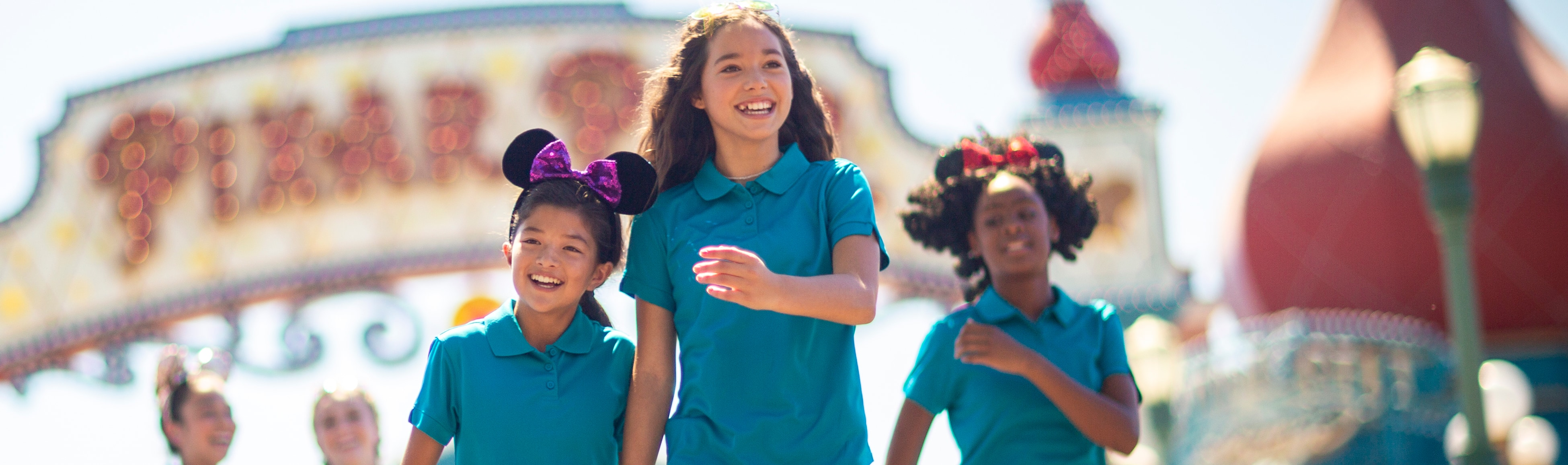 Two young girls in matching outfits hold hands while walking ahead of other girls in similar outfits under a sign that reads, Pixar Pier