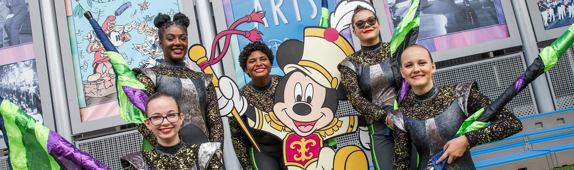 Five women in flag team uniforms posed around a standee of Mickey Mouse as a Drum Major